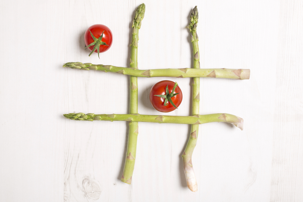 fresh raw asparagus laid out like naughts and crosses game using tomatoes